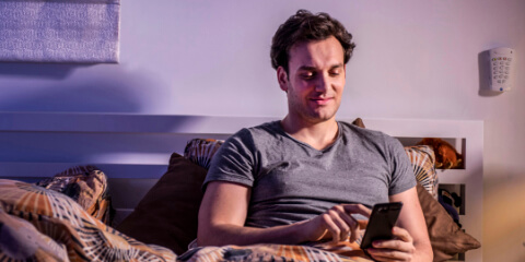 Man browsing his phone in bed