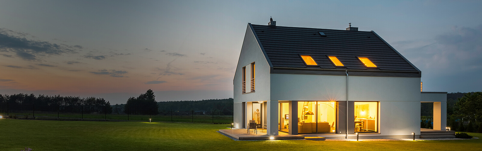 Detached property lit up by its internal and external lighting