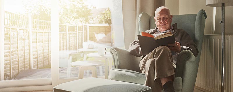 Man in armchair reading a book next to the patio doors