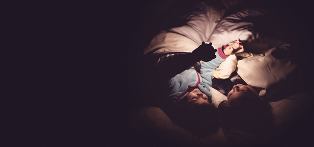 Two children playing in bed at night with a torch small