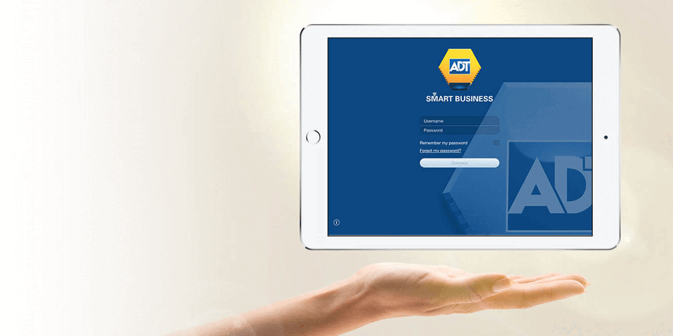 Tablet device showing ADT Smart Business login page hovering above an open hand small