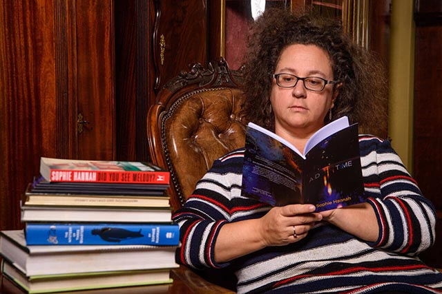 Author Sophie Hannah sat in a chair reading next to a stack of books