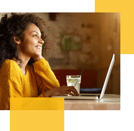 Woman smiling while on her laptop, two yellow blocks are featured in the image