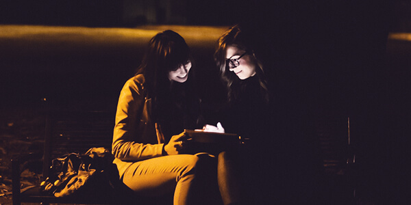 Two women on phones at night mobile