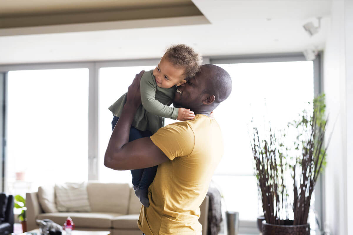 Man lifting up a toddler in a living room