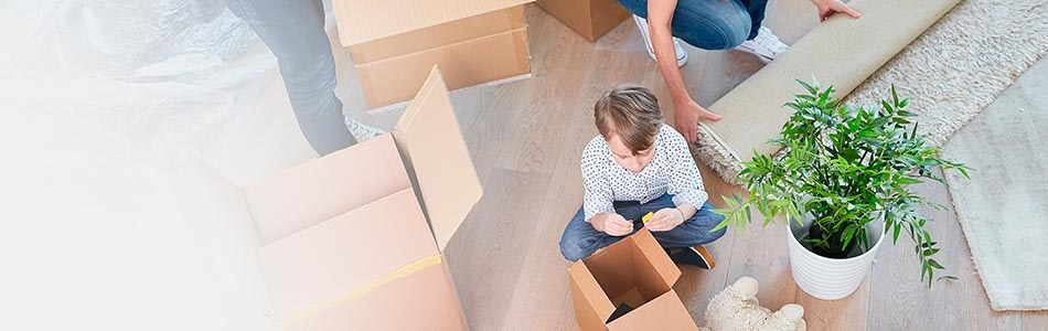 Boy sat on floor playing with toys surrounded by packing boxes