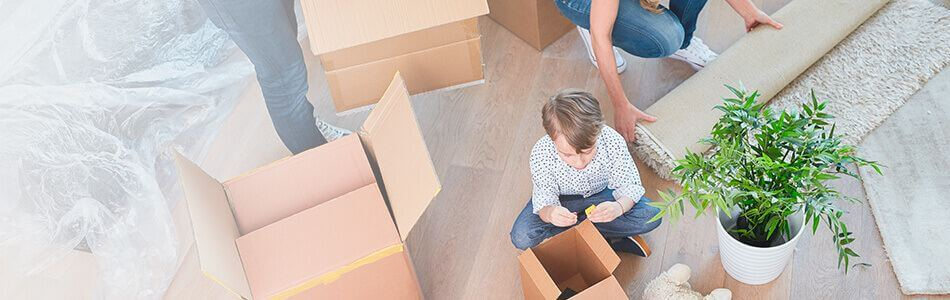 Boy sat on floor playing with toys surrounded by packing boxes small