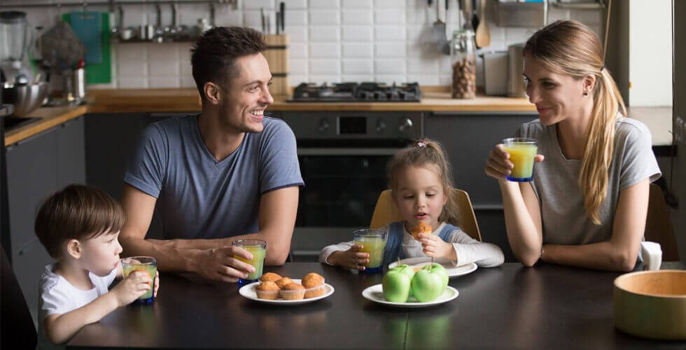 Family with young children sat at a table eating muffins and apples and drinking juice small