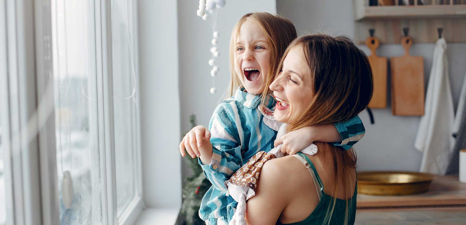 Woman holding young child at a window as both laugh