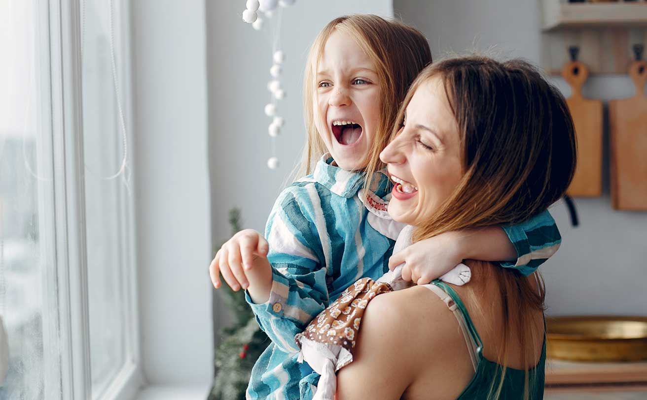 Woman holding young child at a window as both laugh small