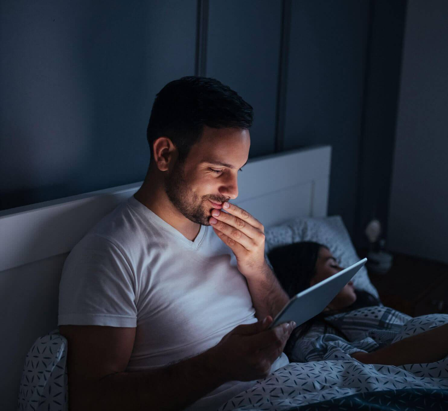 Man sat up in bed next to sleeping woman illumined by tablet screen he is looking at