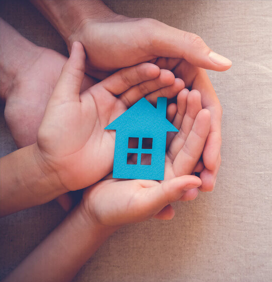 Adult hands support child's hands holding a blue paper cut out of a house
